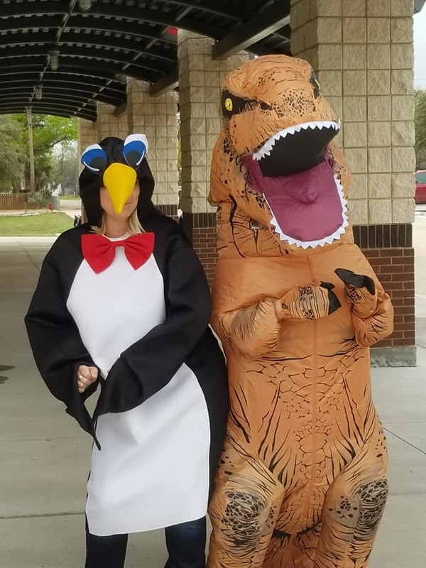 Someone dressed up as a penguin and another dressed up like a T-Rex